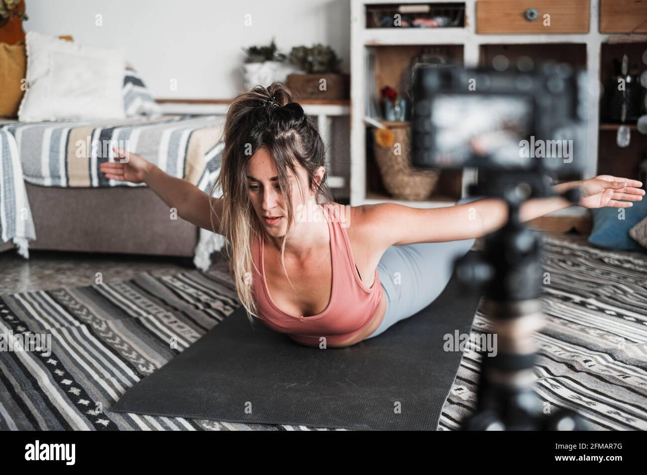 Jeune femme s'exerçant à la maison faisant pilates et l'enregistrement à elle dispose d'un appareil photo numérique pour enseigner l'entraînement et produire du web classe - créateur de contenu affaires libre sain style de vie personnes concept Banque D'Images