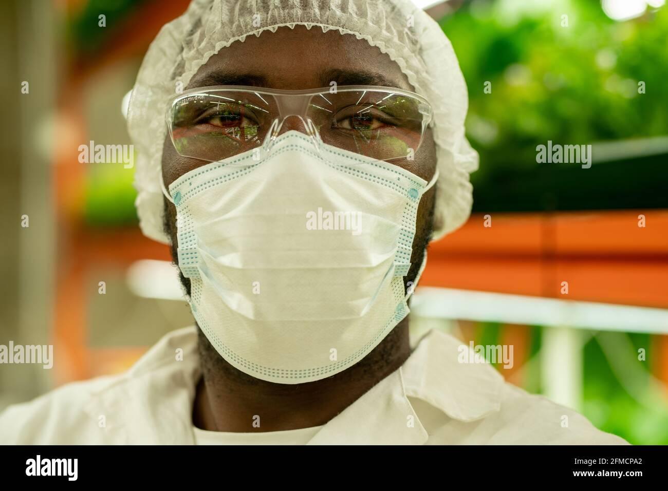 Portrait d'un jeune spécialiste de la culture afro-américaine sérieux en masque, lunettes et casquette debout contre le plateau vertical de la ferme Banque D'Images
