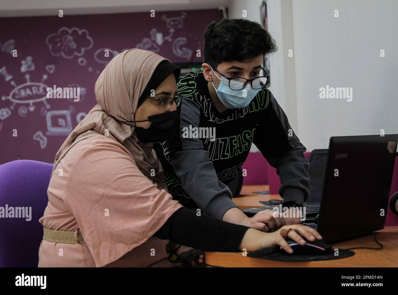 Gaza. 26 avril 2021. Nour al-DIN Fifil (R) travaille sur son ordinateur portable à Gaza, le 26 avril 2021. Nour al-DIN Fifil, un enfant palestinien de la ville de Gaza, est connu pour ses compétences en programmation et en conception de jeux électroniques. POUR ALLER AVEC 'Feature: Gazan enfant excelle dans la programmation, la conception de jeux électroniques' Credit: Rizek Abdeljawad/Xinhua/Alay Live News Banque D'Images