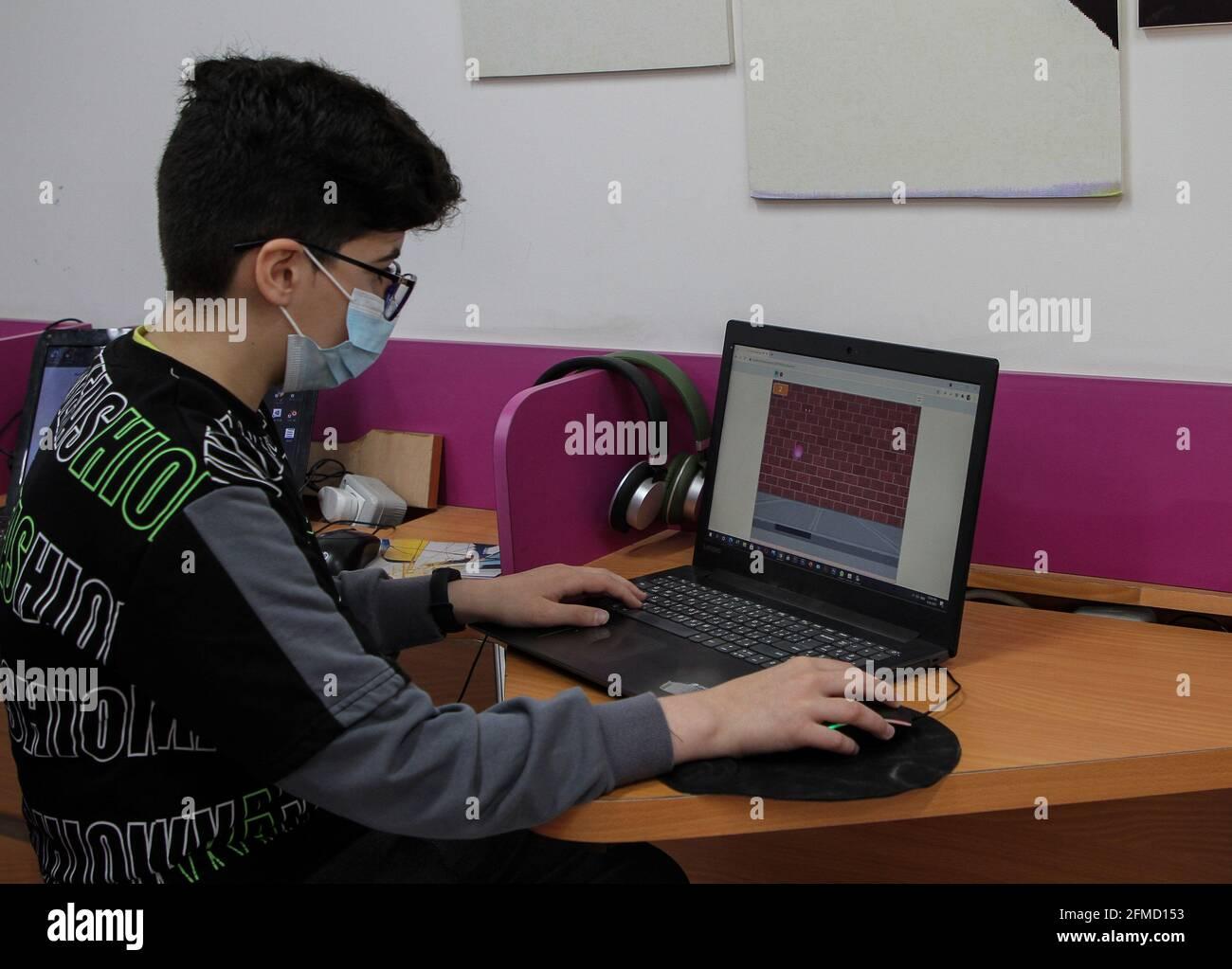 Gaza. 26 avril 2021. Nour al-DIN Fifil travaille sur son ordinateur portable à Gaza, le 26 avril 2021. Nour al-DIN Fifil, un enfant palestinien de la ville de Gaza, est connu pour ses compétences en programmation et en conception de jeux électroniques. POUR ALLER AVEC 'Feature: Gazan enfant excelle dans la programmation, la conception de jeux électroniques' Credit: Rizek Abdeljawad/Xinhua/Alay Live News Banque D'Images