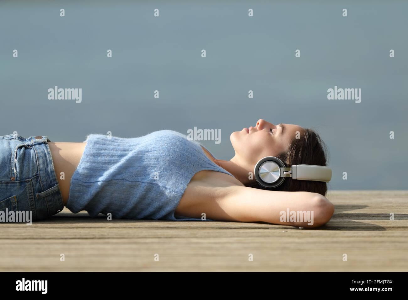 Profil d'une femme qui porte un casque sans fil et qui se détend musique sur un quai de lac Banque D'Images