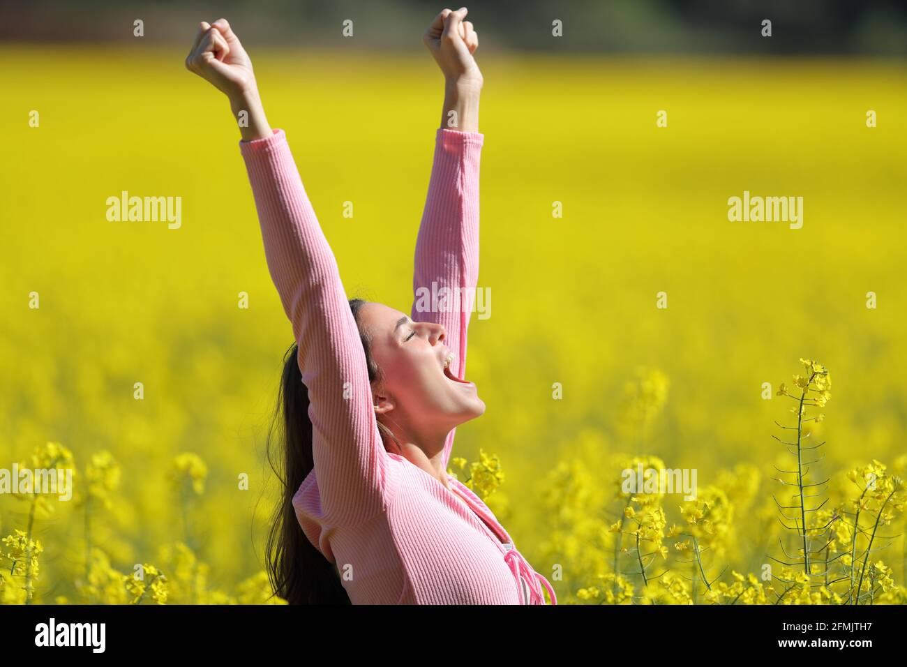 Vue latérale d'une femme excitée qui soulève les bras un champ jaune au printemps Banque D'Images