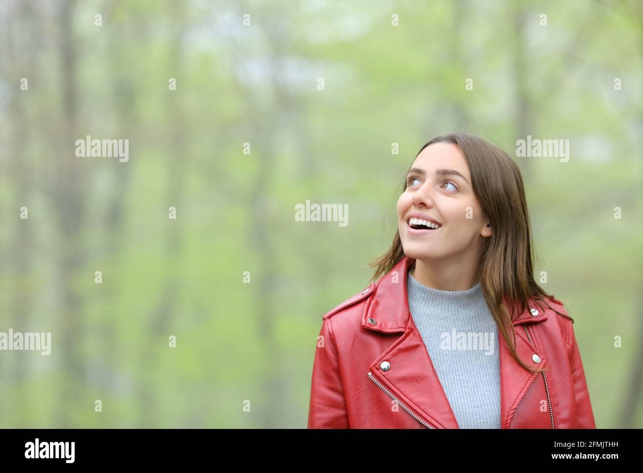 Femme émerveillement en rouge contemplant la marche dans une forêt Banque D'Images