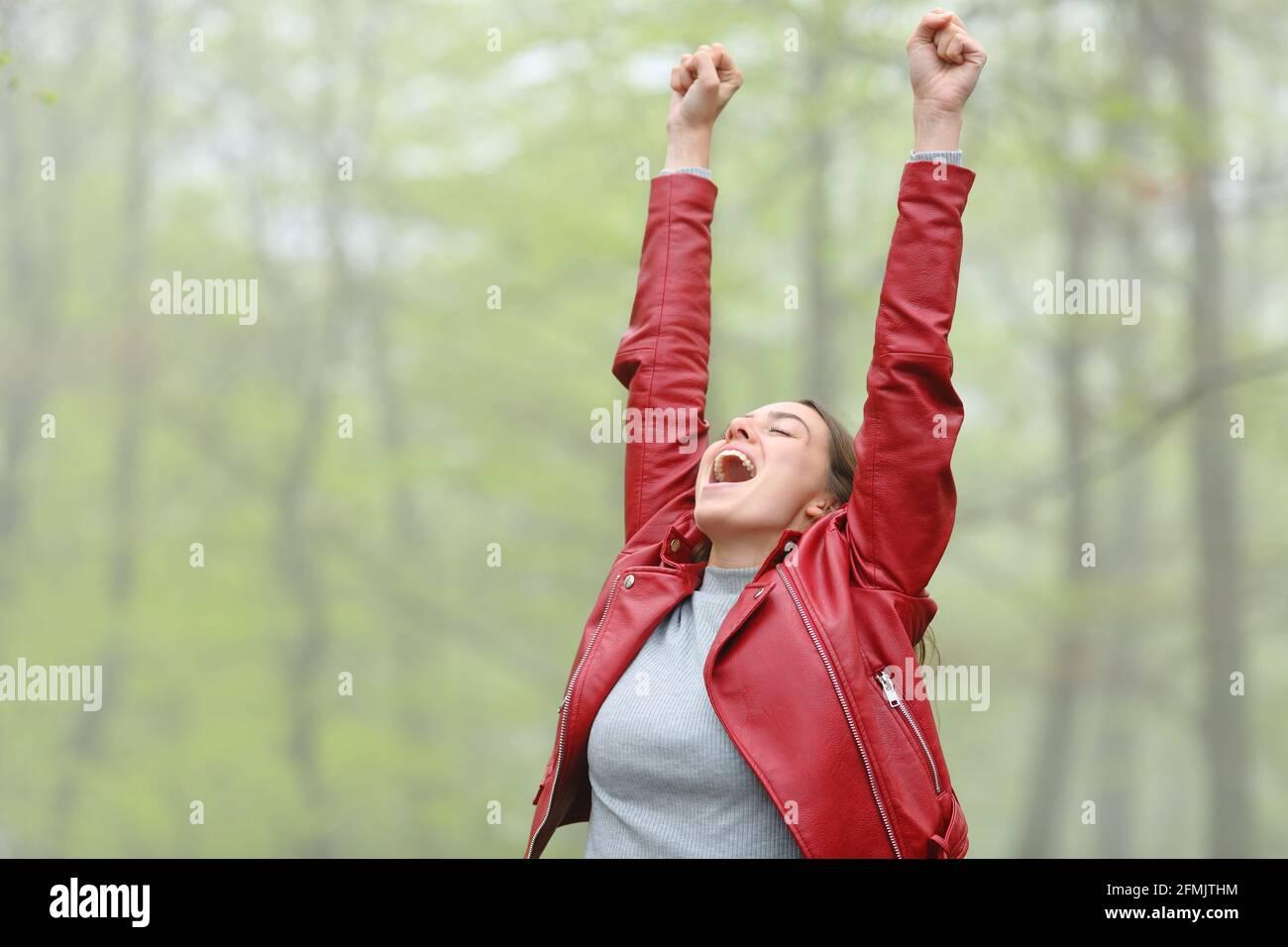 Femme en rouge excitée de lever des armes criant dans une forêt Banque D'Images