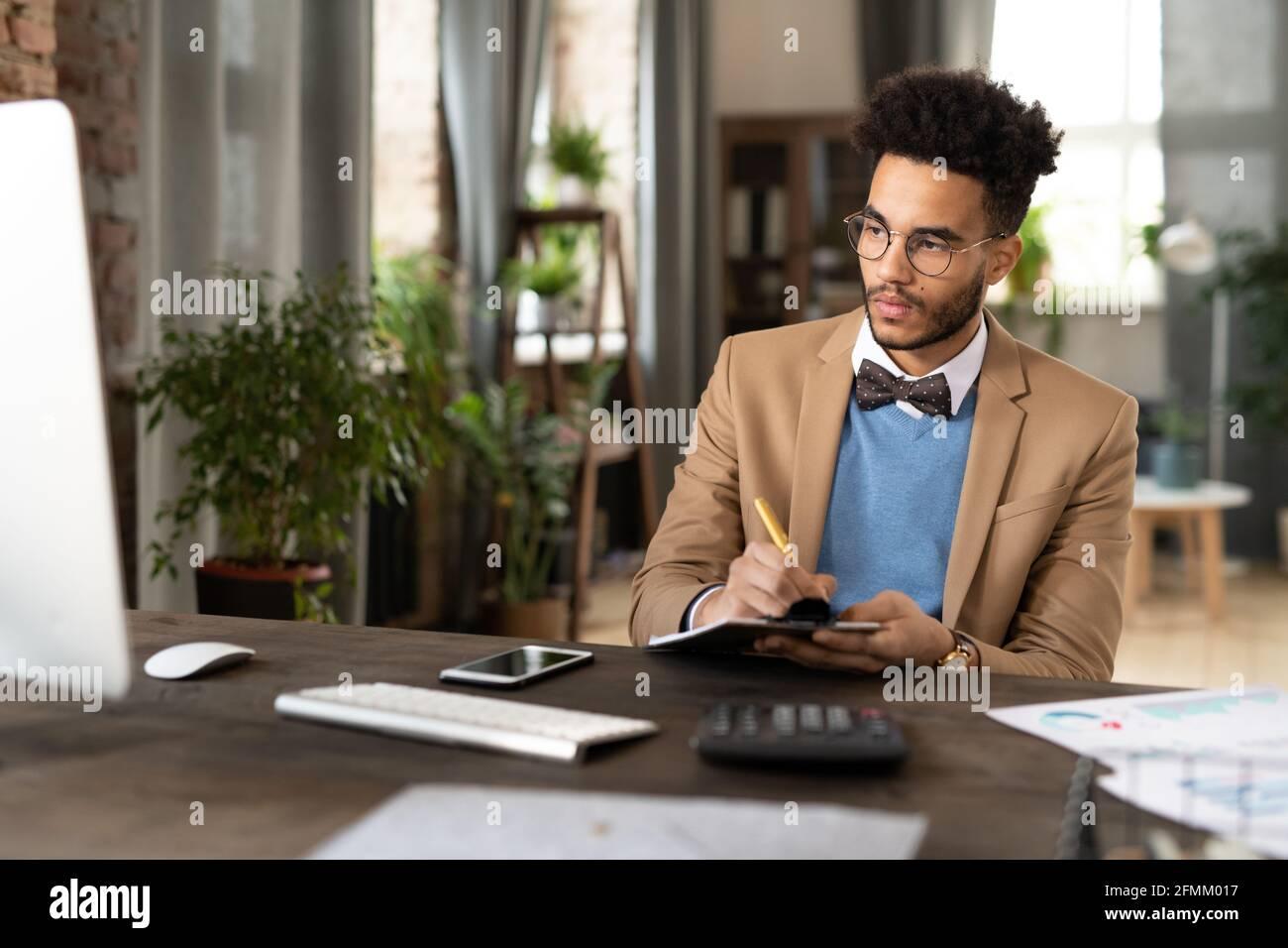 Jeune financier noir concentré avec barbe assis sur un bureau en bois avec la calculatrice et prendre des notes dans le bloc-notes lors de l'analyse des données sur l'ordinateur Banque D'Images