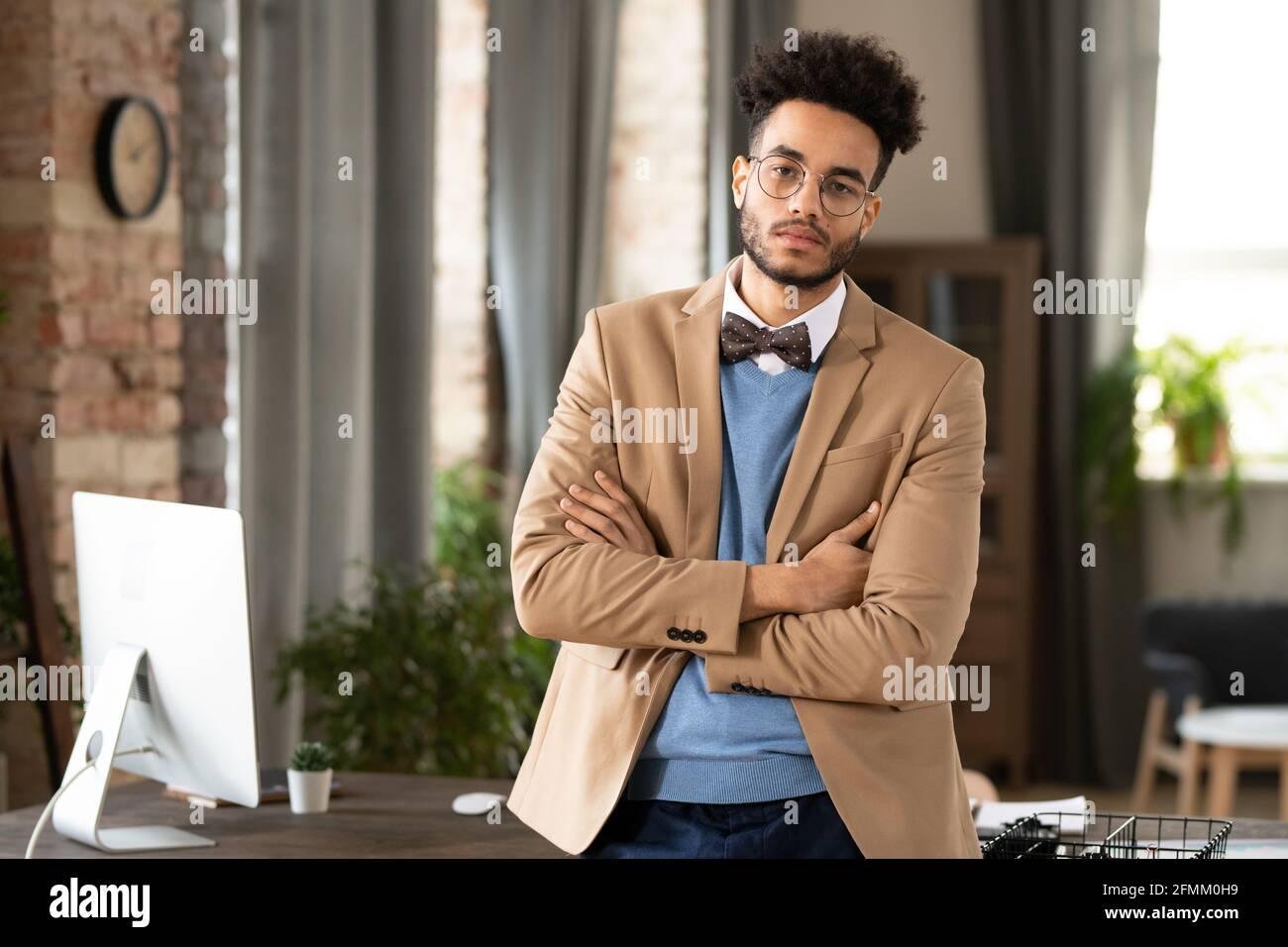 Portrait d'un Manager afro-américain confiant avec une barbe debout bras croisés contre la table avec un ordinateur moderne dans un bureau confortable Banque D'Images