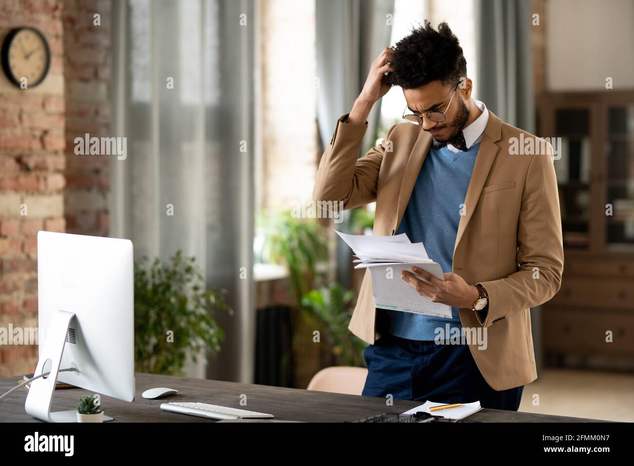 Jeune homme de course mixte confus en lunettes et veste debout au bureau avec ordinateur et en se grattant la tête tout en lisant des journaux Banque D'Images