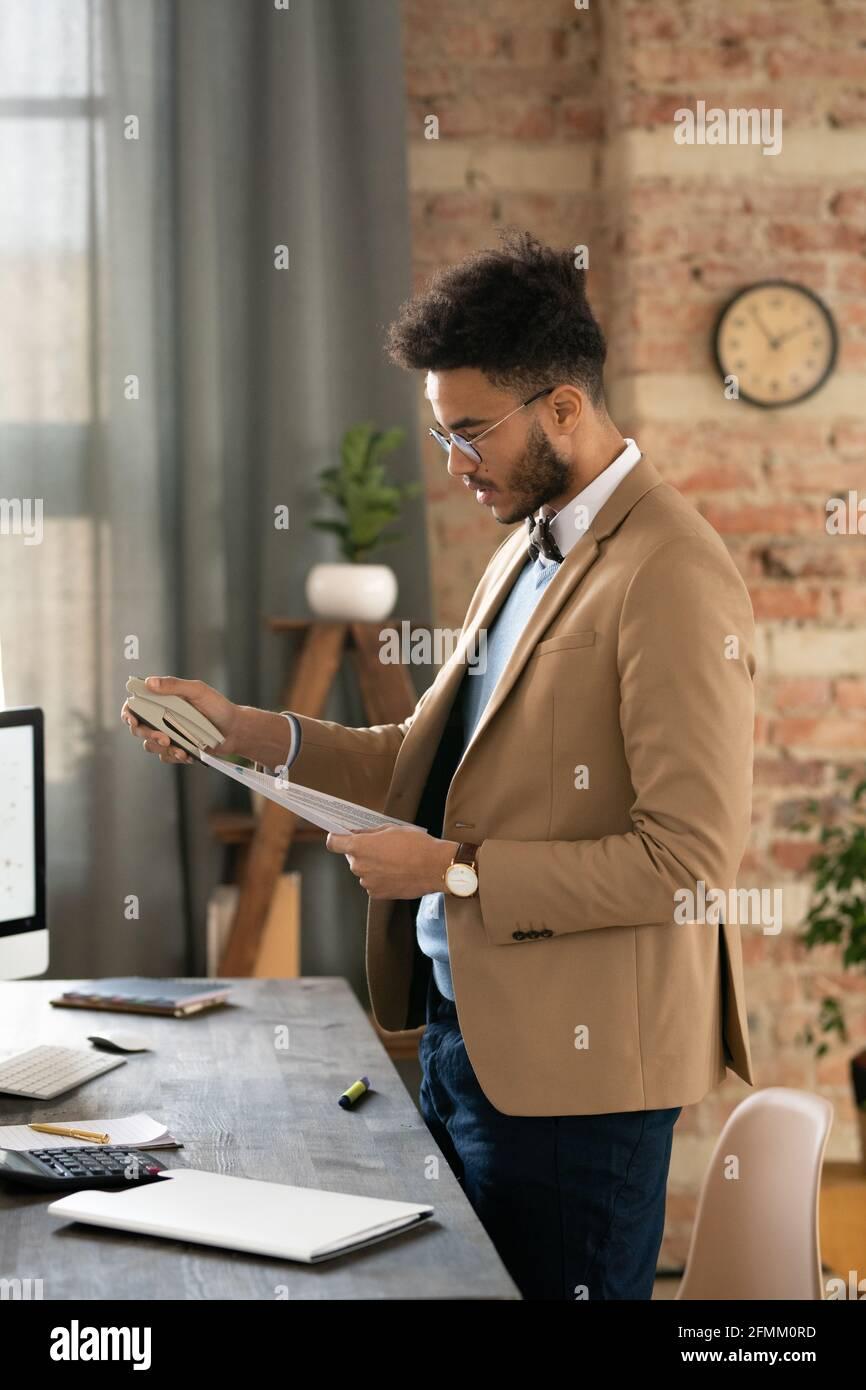 Jeune homme d'affaires sérieux et mixte avec une barbe debout à son bureau avec calculatrice et papiers d'agrafage au bureau Banque D'Images