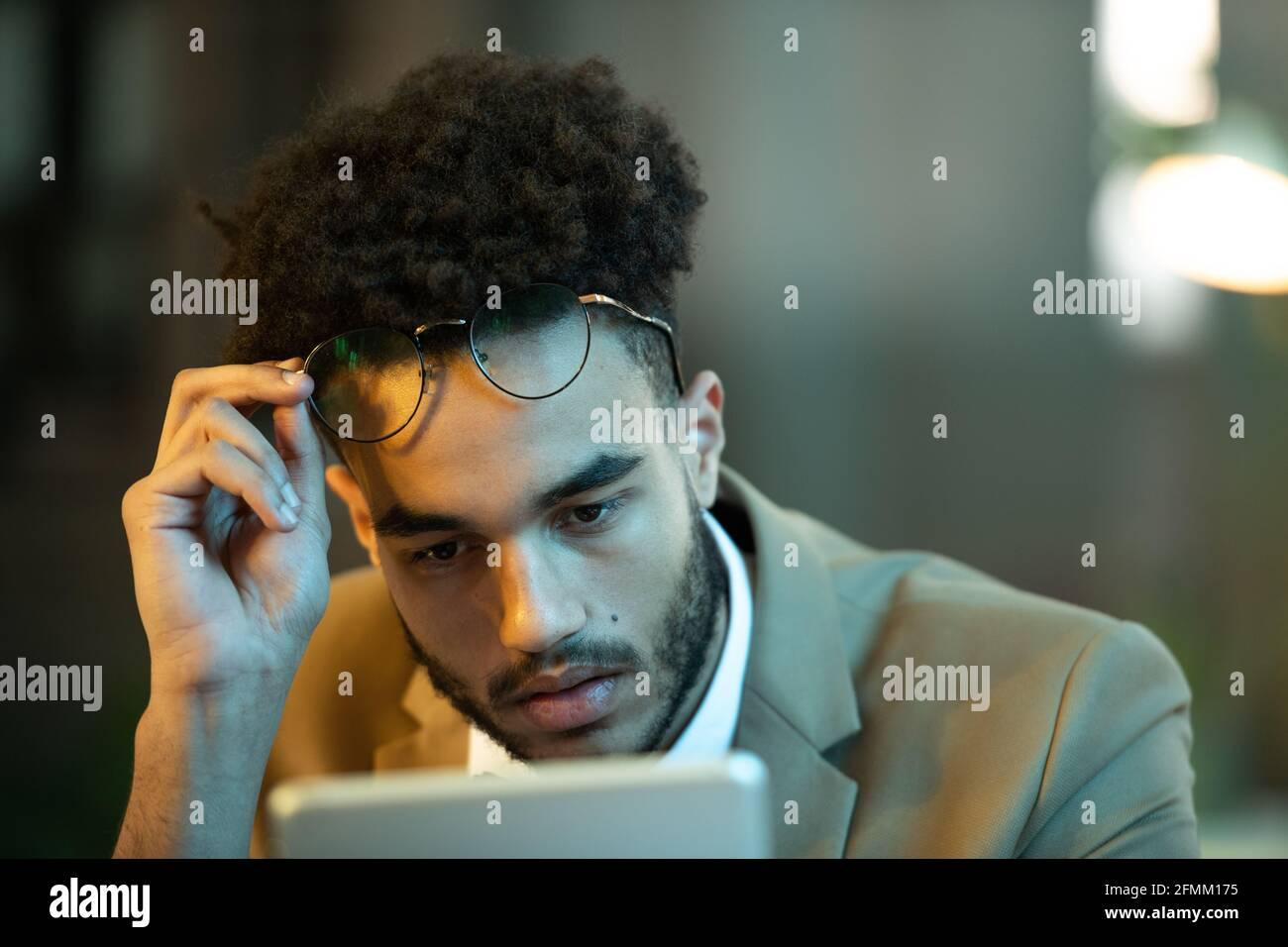 Occupé jeune noir Manager avec la coiffure d'afro prenant des lunettes tout en lisant l'article sur la tablette, il travaille tard Banque D'Images