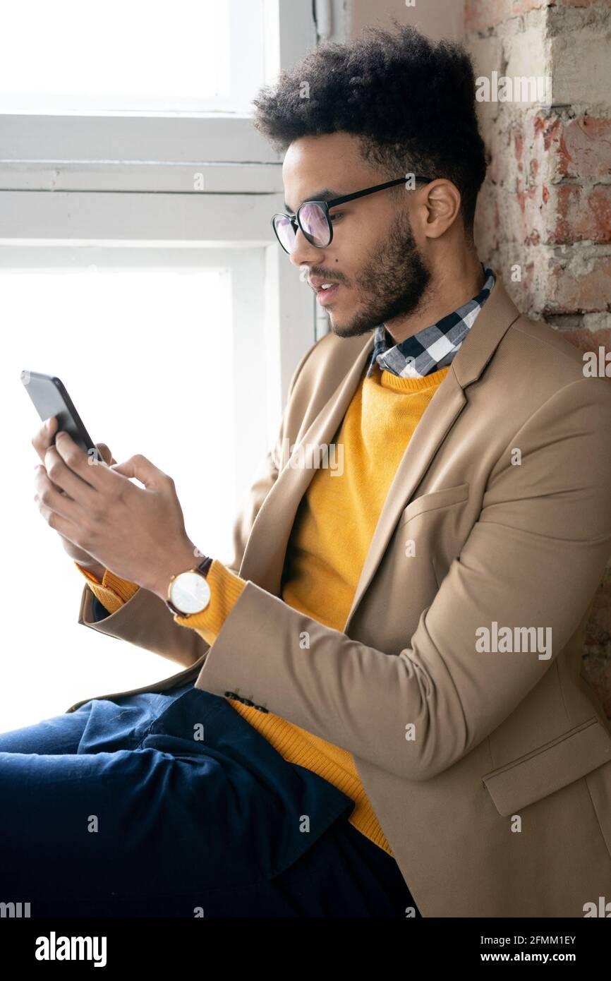 Jeune barbu sérieux dans des lunettes assis sur le rebord de la fenêtre et envoyer des sms sur le téléphone en travaillant en ligne Banque D'Images