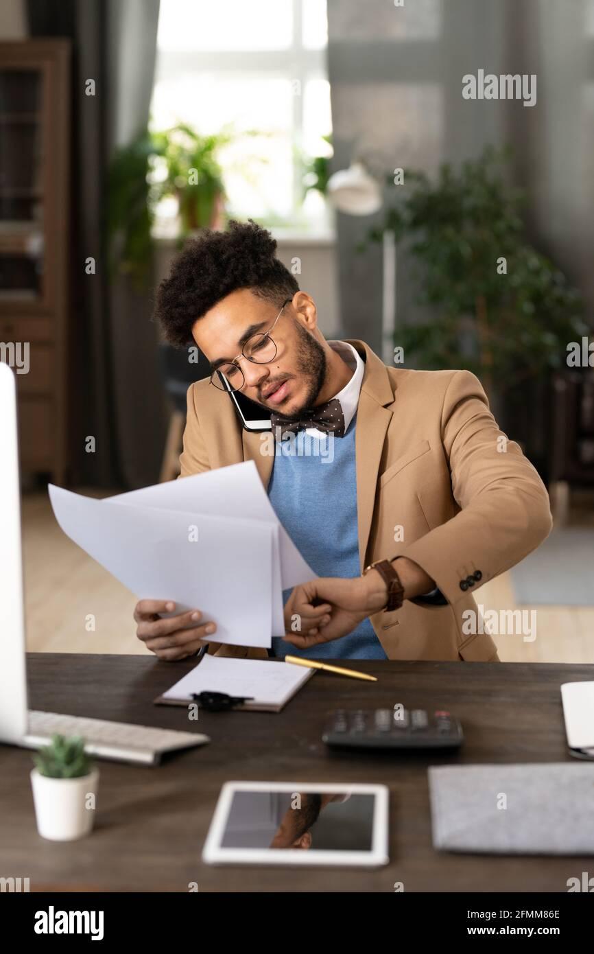 Un directeur de course mixte multitâche sérieux en nœud papillon assis à table avec une calculatrice et en vérifiant le temps tout en parlant par téléphone et en examinant des papiers. Banque D'Images