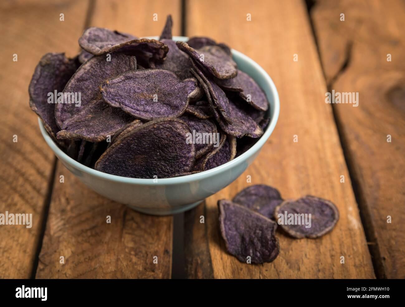 Chips de pommes de terre à base de pommes de terre violettes dans un bol turquoise sur une table en bois rustique Banque D'Images