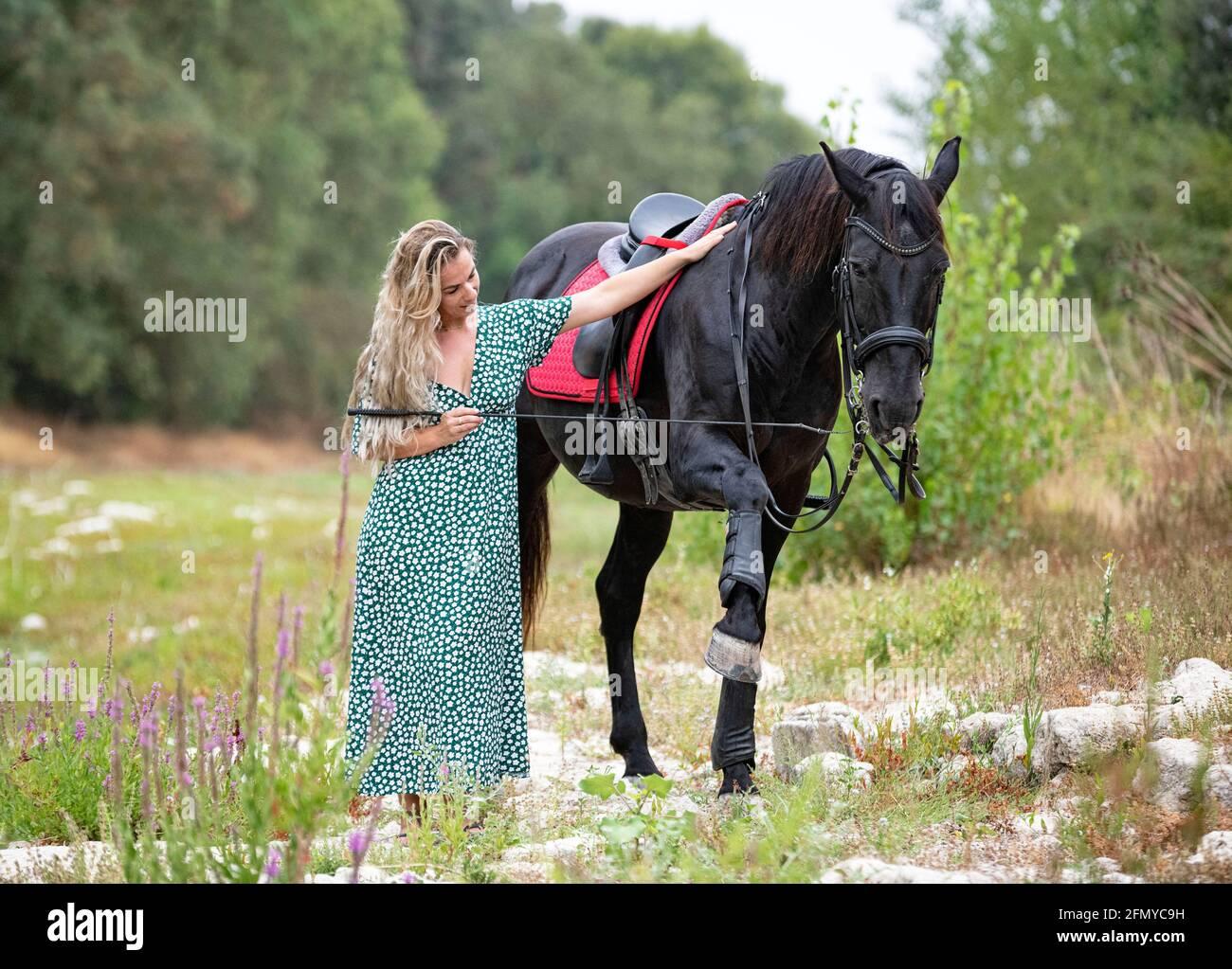 une fille d'équitation marche avec son cheval noir Banque D'Images