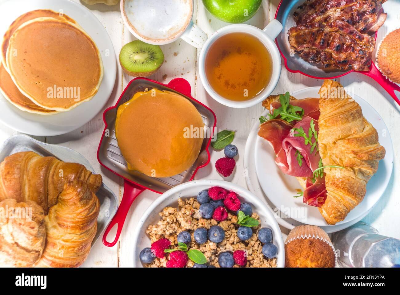 Divers plats traditionnels pour le petit déjeuner - œufs frits avec bacon, muesli, avoine, gaufres, crêpes, hamburger, croissants, fruits, café, thé et orange j Banque D'Images