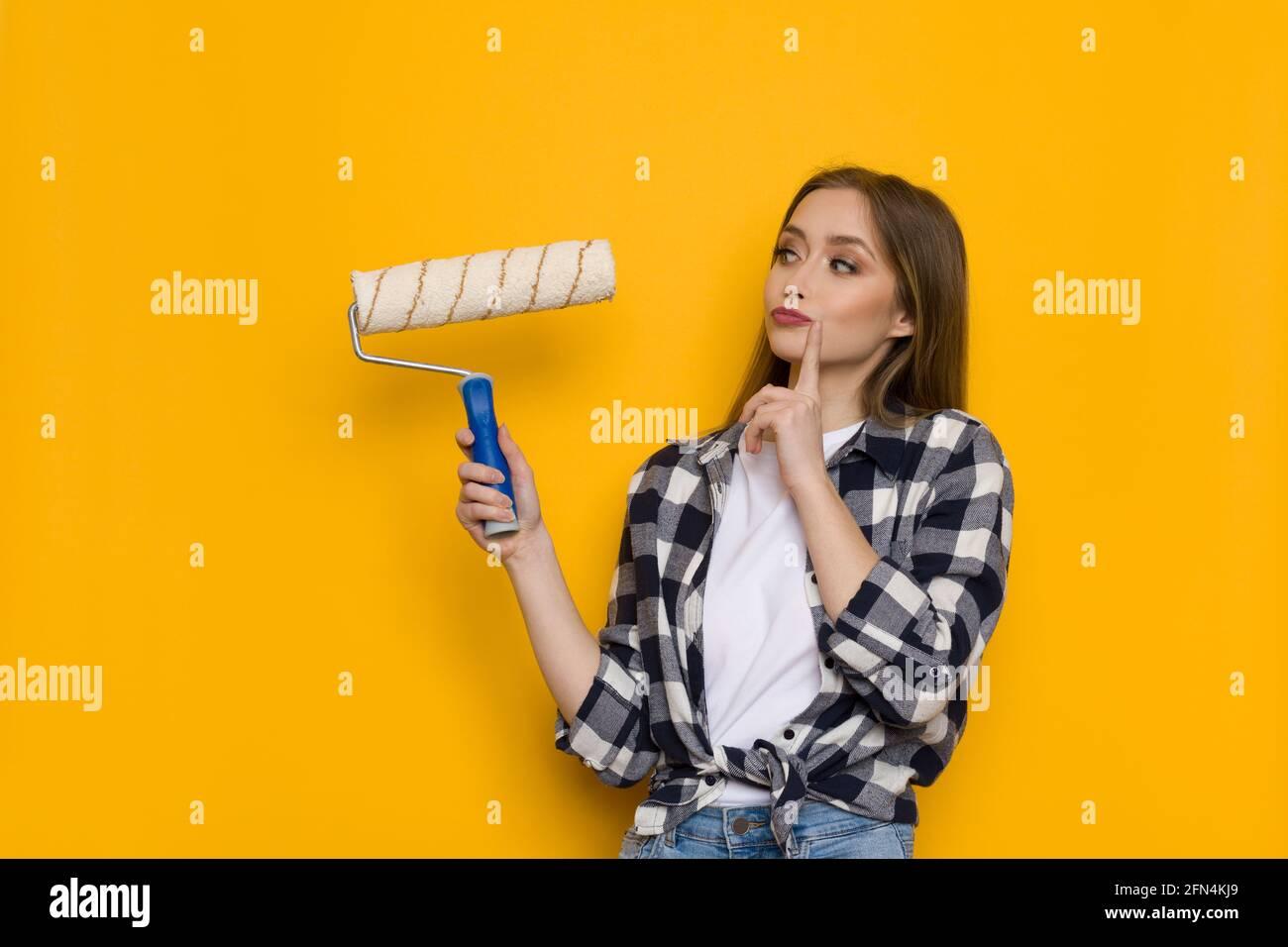 Jeune femme blonde en chemise de bûcherons tient le rouleau de peinture et de penser. Taille relevée sur fond jaune Banque D'Images