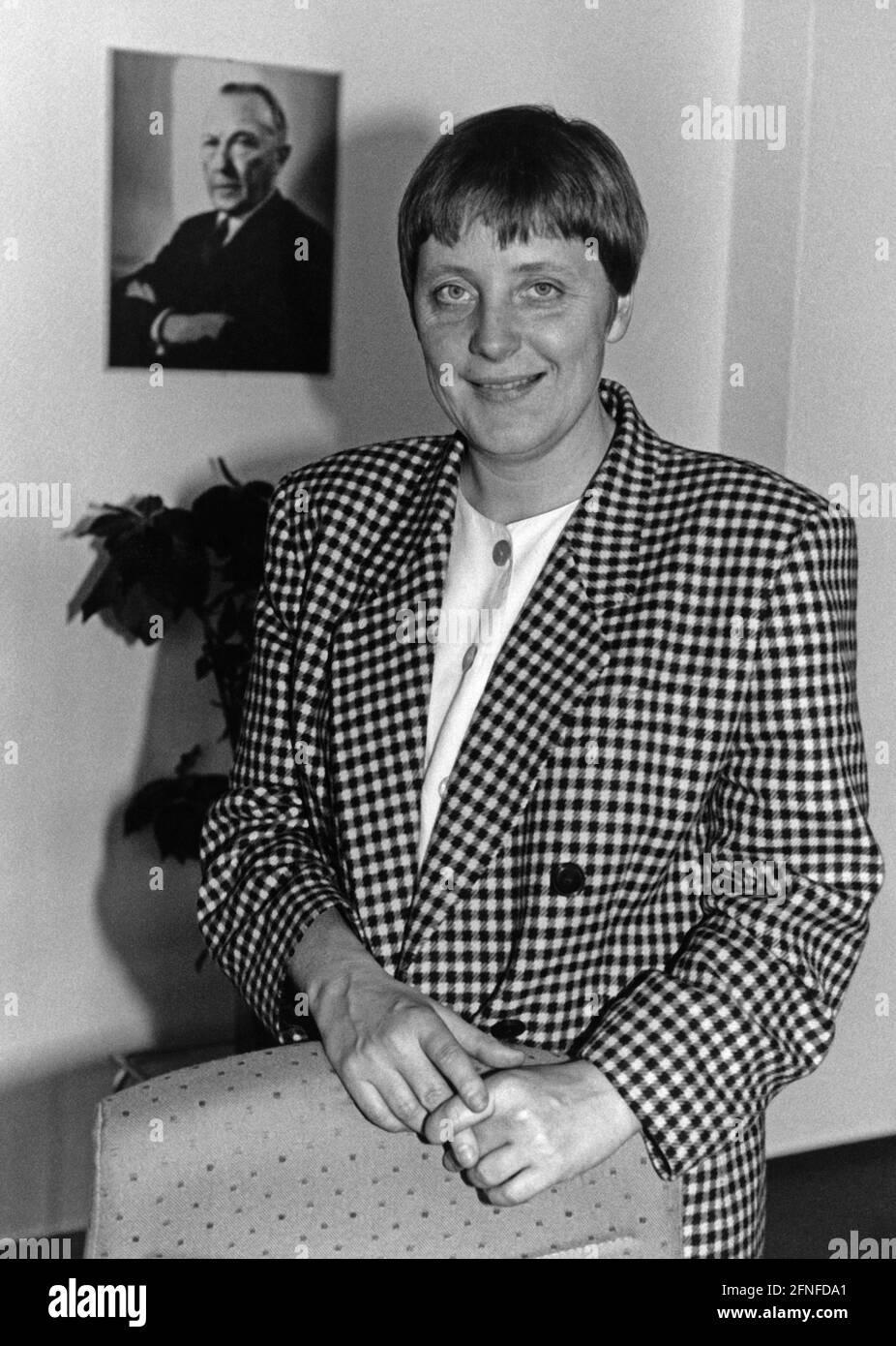 angela-merkel-ministre-federale-de-la-femme-et-de-la-jeunesse-dans-son-bureau-devant-la-photo-de-konrad-adenauer-photographie-non-datee-env-1991-traduction-automatique-2fnfda1.jpg