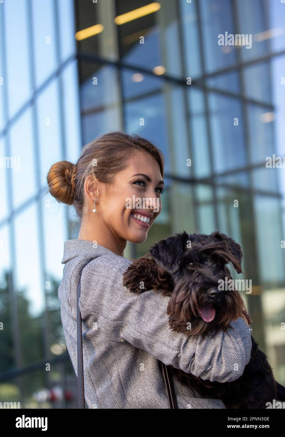 Jolie jeune femme d'affaires tenant un chien mignon dans les bras devant le bâtiment des bureaux Banque D'Images