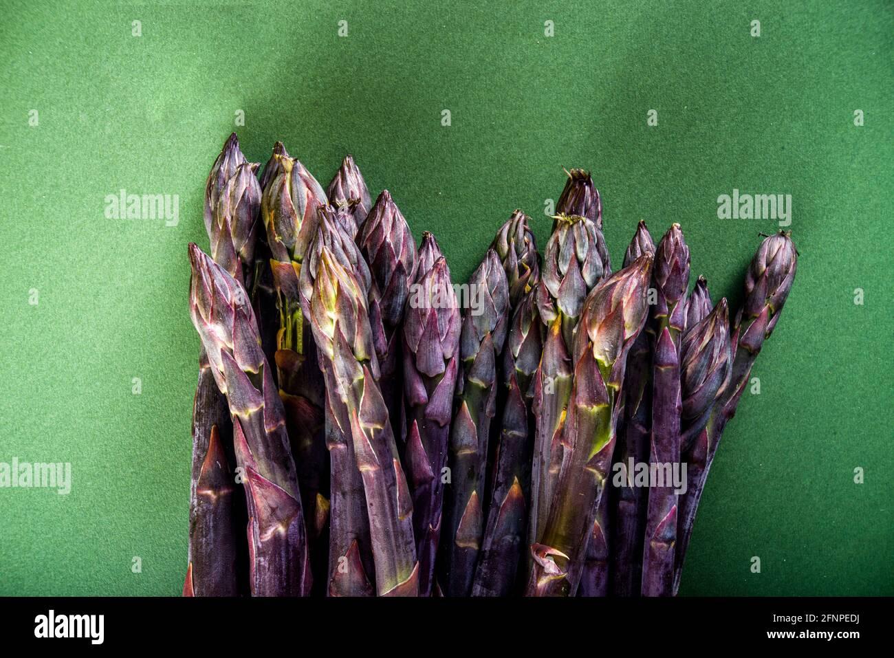 Bouquet d'asperges fraîches, crues, légumes violets, verts et blancs sur fond vert foncé Banque D'Images