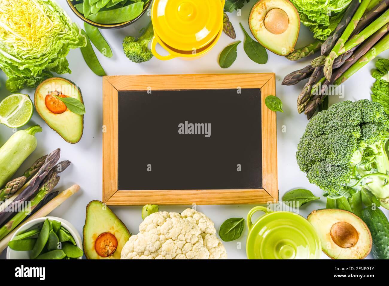 Divers ingrédients biologiques de légumes de printemps verts avec pots de cuisson colorés vides sur table de cuisine blanche, vue du dessus. Soupe saine alimentation, ste Banque D'Images
