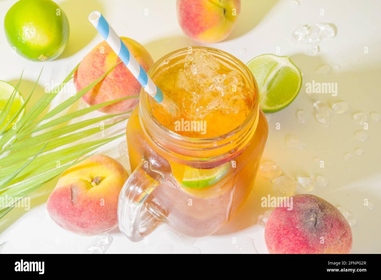 Boisson fraîche d'été, cocktail traditionnel de thé de pêche glacé avec glace pilée, tranches de pêche et citron, sur fond jaune ensoleillé et branché Banque D'Images