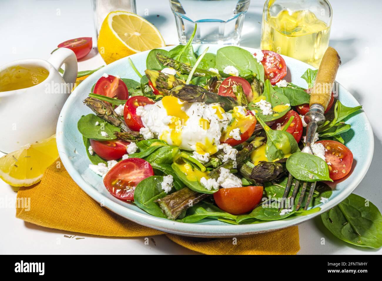 Nourriture saine végétalienne, salade d'asperges chaudes avec des jeunes épinards, tomates cerises, fromage feta et œuf poché, lumière bleue lumière sur fond vue du dessus c Banque D'Images