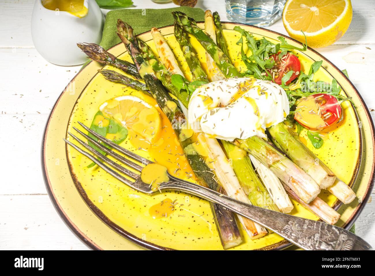 Nourriture saine, asperges grillées au four, œuf poché et sauce hollandaise sur fond de bois blanc espace copie vue du dessus Banque D'Images