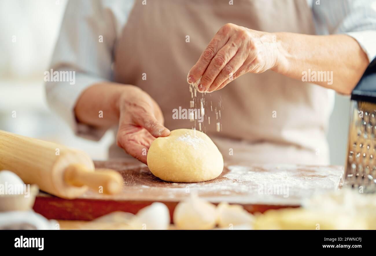 Vue rapprochée du boulanger en cours. Pain maison. Mains préparant la pâte sur une table en bois. Banque D'Images