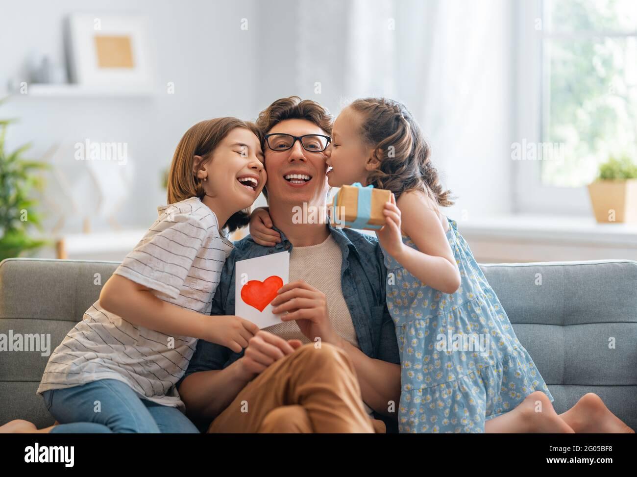 Les enfants filles félicitaient leur père et lui donnent une carte postale. Papa et les filles sont souriantes et embrassantes. Vacances en famille et ensemble. Banque D'Images