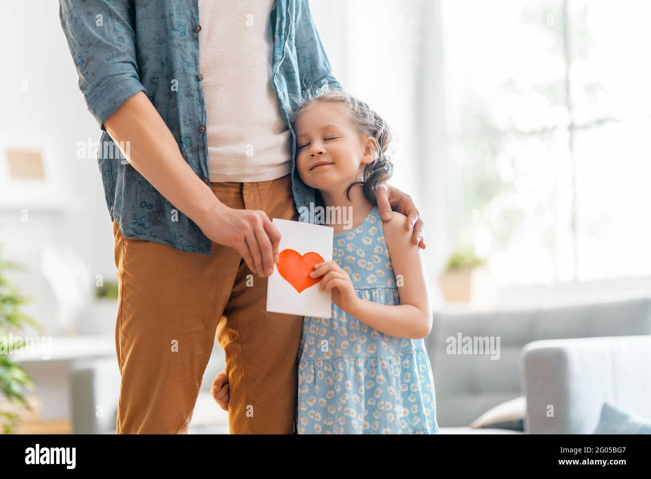 L'enfant fille félicite son père et lui donne une carte postale. Papa et fille sont souriants et embrassant. Vacances en famille et ensemble. Banque D'Images
