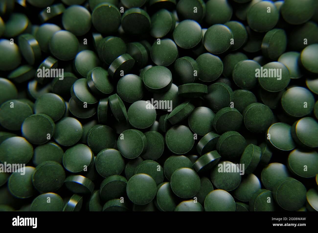 Spiruline vert pilules fond. Comprimés verts d'algues Spirulina. Compléments alimentaires pour un mode de vie sain Banque D'Images
