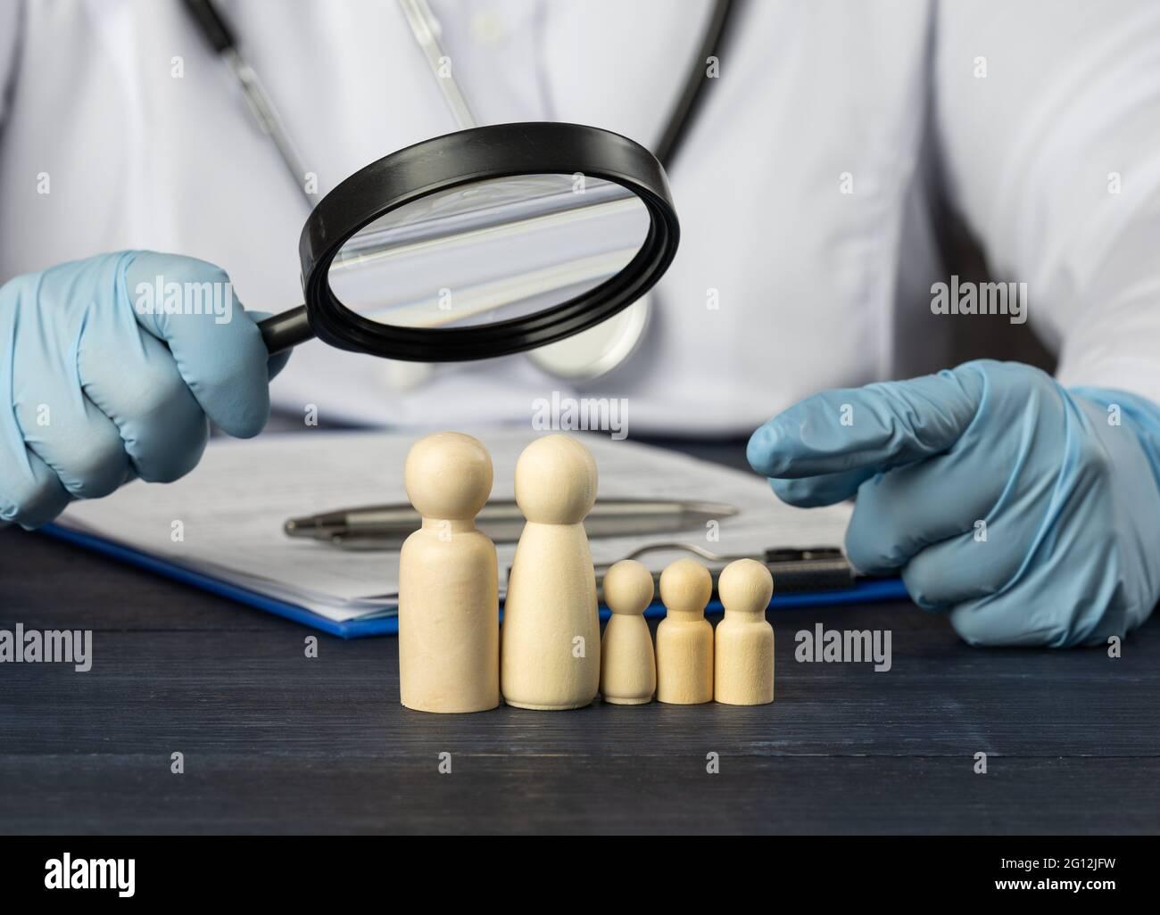 le médecin de famille tient une loupe sur une figurine en bois. Concept de recherche médicale, méthodes de traitement. La nécessité d'une assurance médicale. Banque D'Images