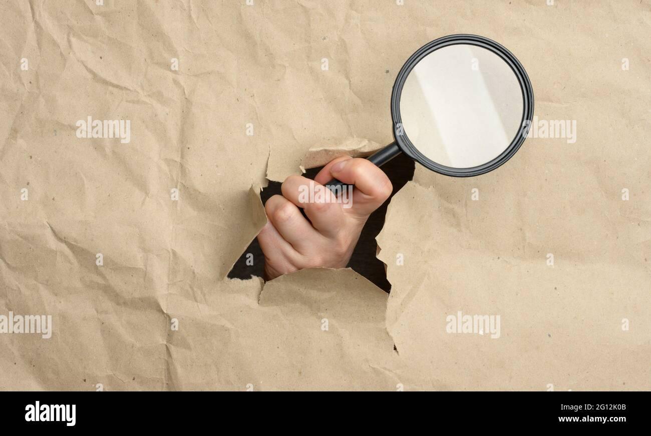 la main d'une femme tient une loupe en verre, une partie du corps dépasse d'un trou en papier brun. Concept de recherche de solution, recherche. Banque D'Images