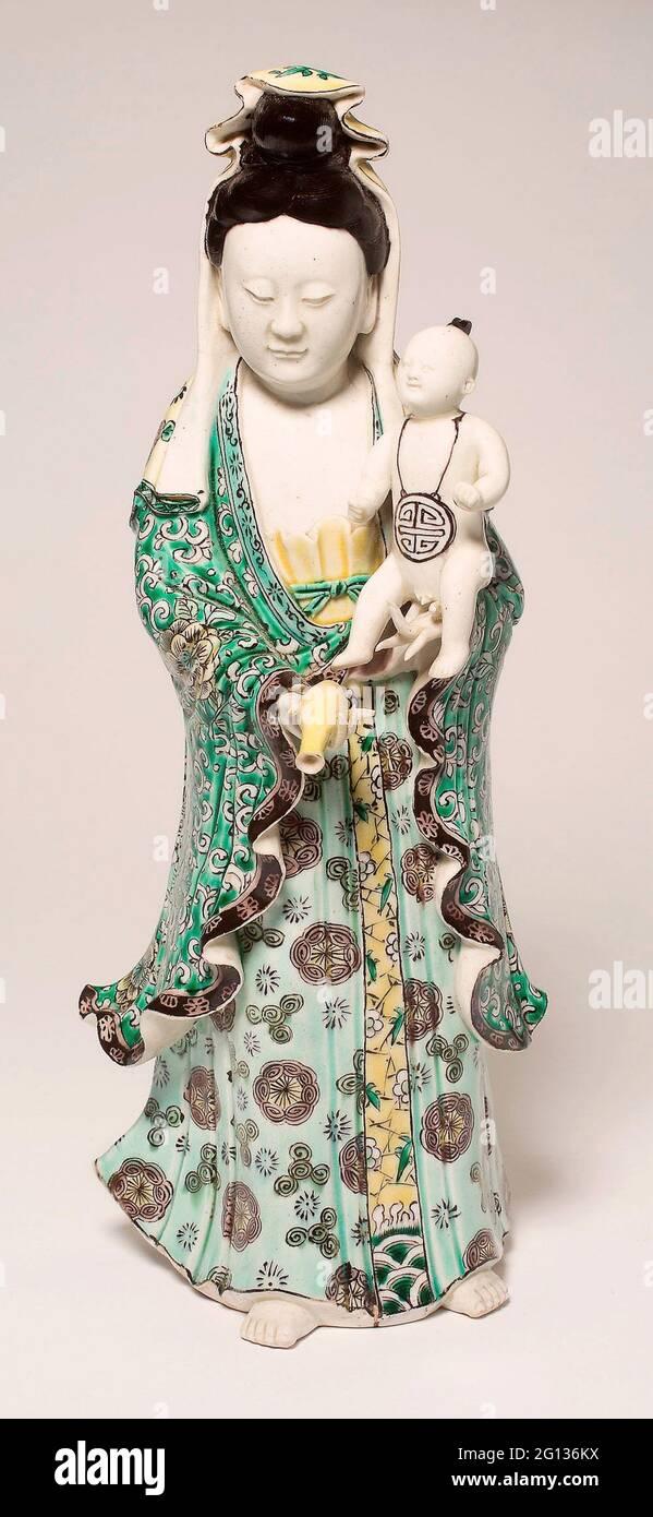 Guanyin tenant un bébé - dynastie Qing (1644 - 1911) - Chine. Porcelaine avec émail de la famille verte sur le biscuit. Banque D'Images