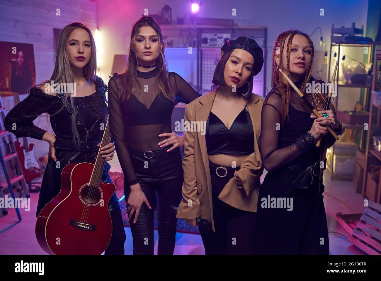 Rangée de musiciens féminins contemporains debout dans un studio de disques sonores Banque D'Images