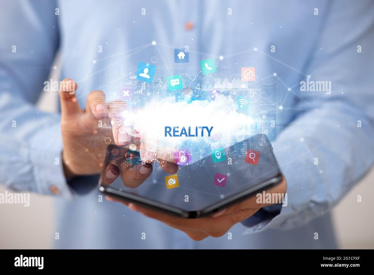Homme d'affaires tenant un smartphone pliable, concept de technologie Banque D'Images