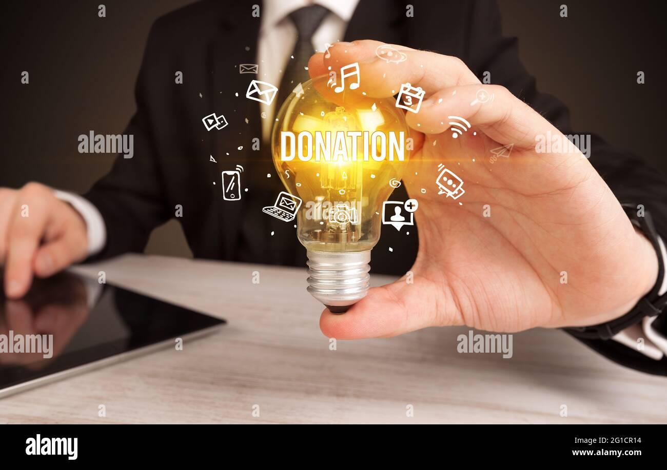 Homme d'affaires tenant une ampoule, concept de médias sociaux Banque D'Images