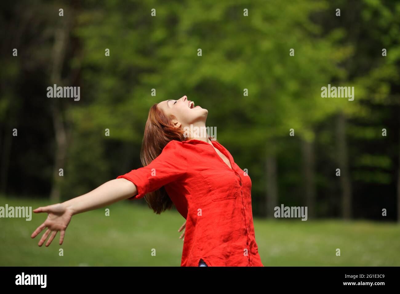 Femme excitée en rouge criant à l'air étirant les bras dans une forêt Banque D'Images
