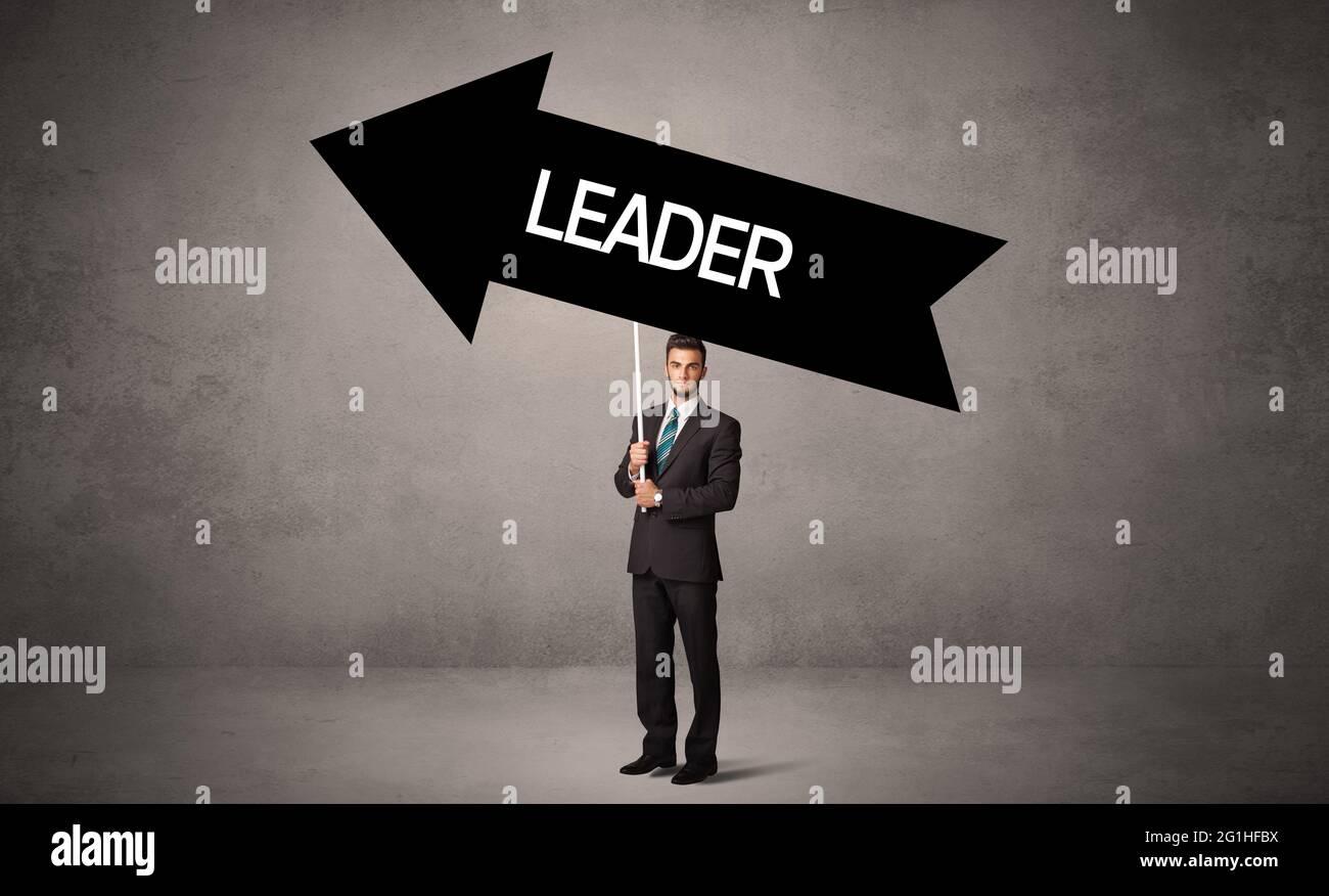 Un jeune homme d'affaires est dans un panneau de route de tenue décontractée Banque D'Images