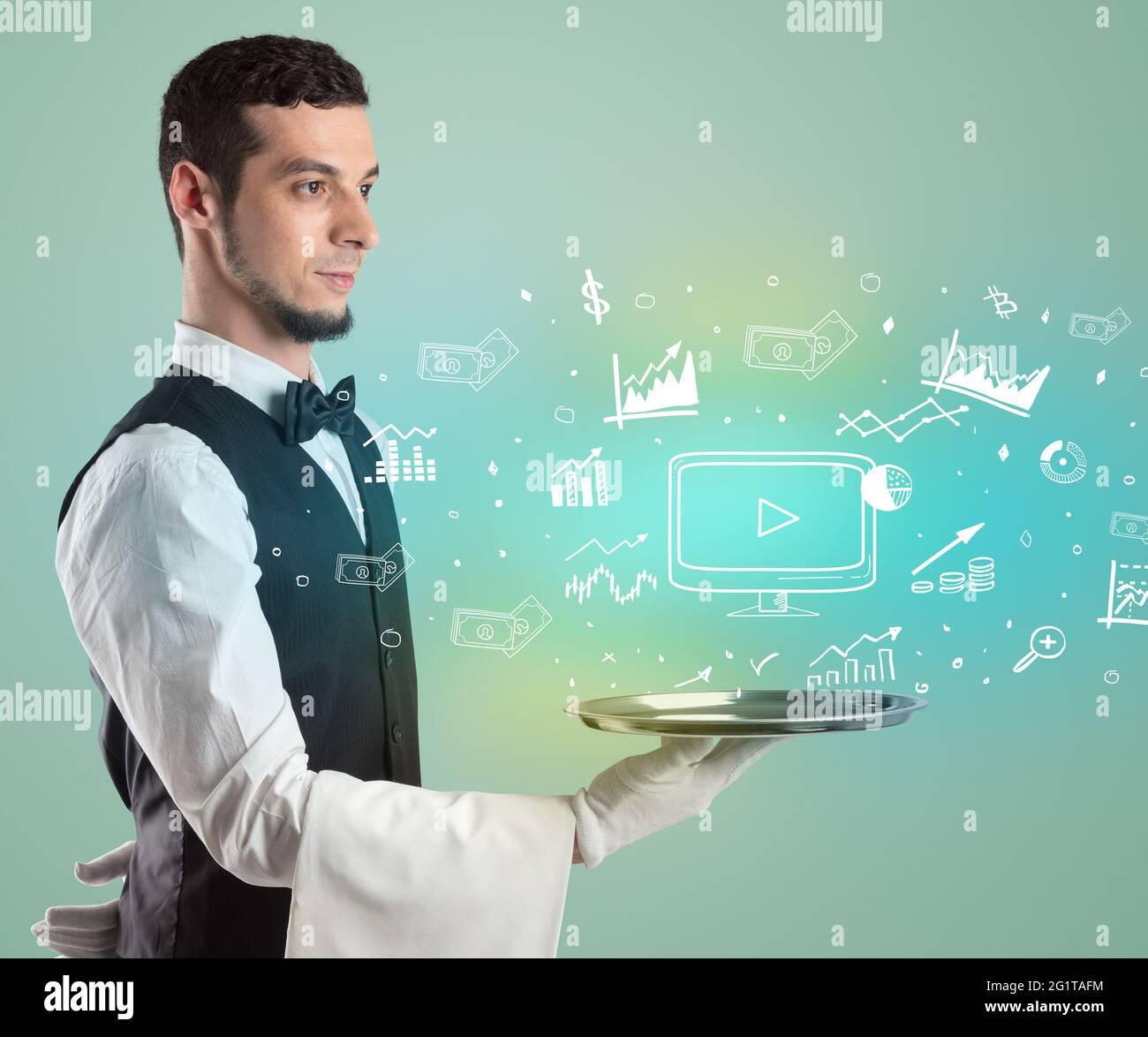 Beau jeune serveur en tuxedo tenant des icônes d'argent sur le plateau Banque D'Images