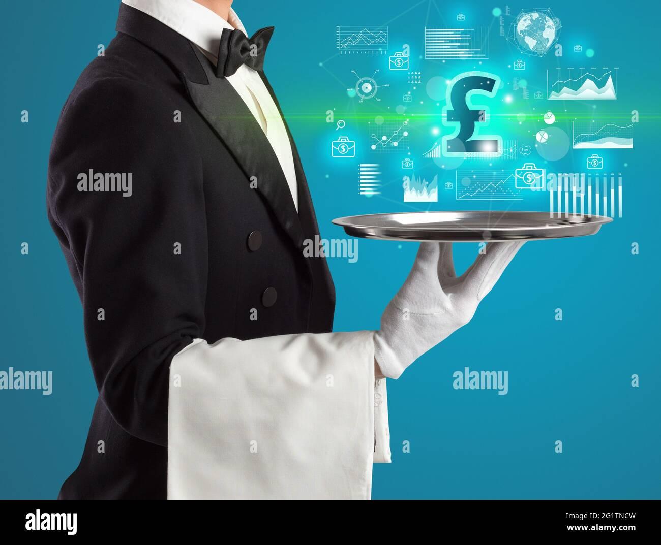 Beau jeune serveur en tuxedo tenant des icônes de devise sur le plateau Banque D'Images