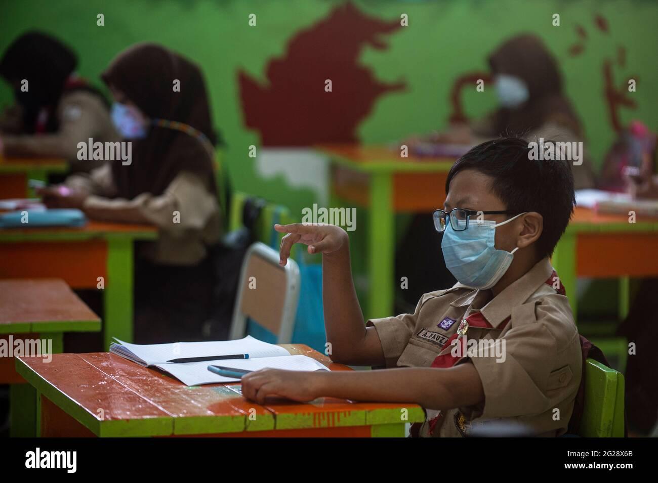 Jakarta, Indonésie. 9 juin 2021. Un élève élémentaire portant un masque facial est vu dans une salle de classe au cours d'une activité d'apprentissage face-à-face d'essai dans le cadre de l'épidémie de COVID-19 dans une école de Jakarta, Indonésie, le 9 juin 2021. Credit: Agung Kuncahya B./Xinhua/Alay Live News Banque D'Images