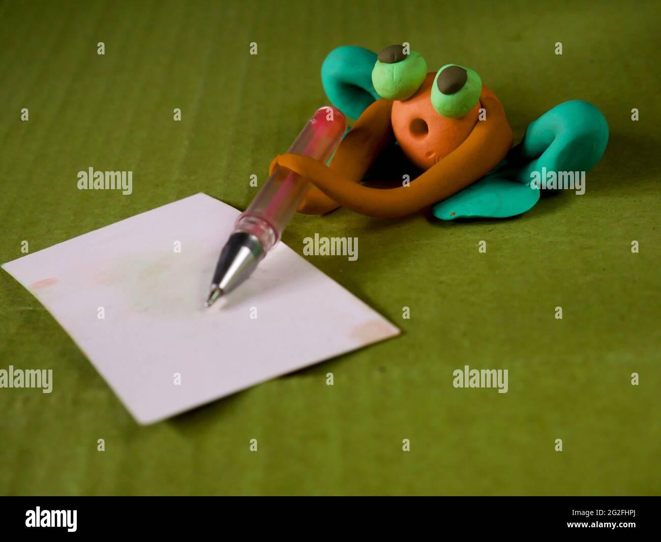 Drôle de grenouille d'argile tenant stylo écriture sur le concept d'éducation de carte blanche Banque D'Images
