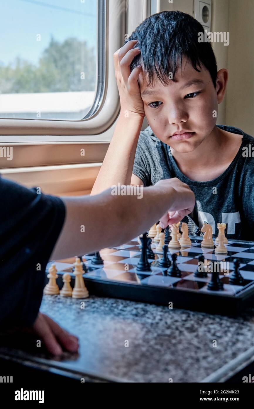 Jeunes garçons jouant aux échecs dans le train Banque D'Images