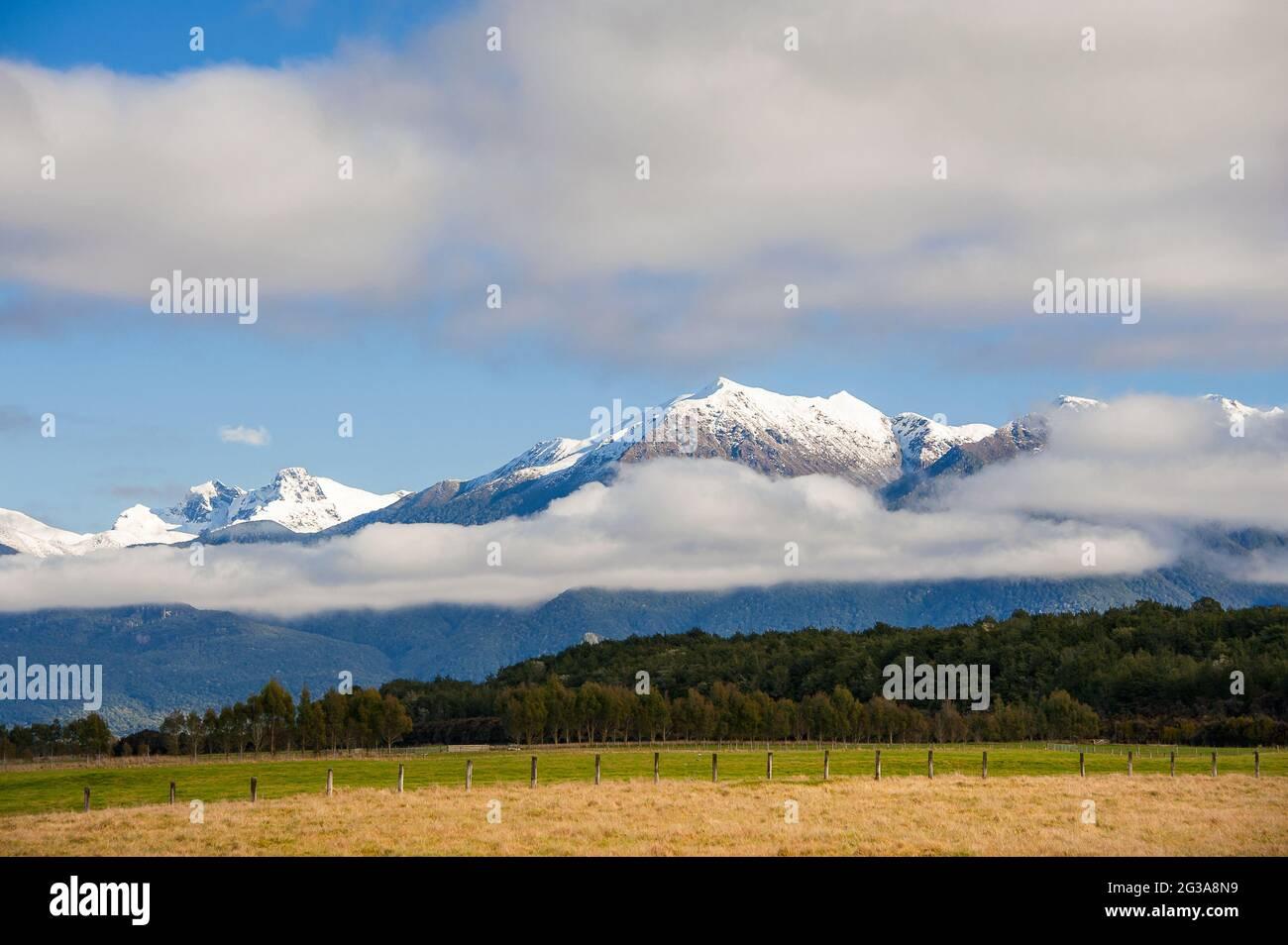 Paysage rural, te Anau, Île du Sud, Nouvelle-Zélande. Vue panoramique, chaîne de montagnes enneigée avec nuages bas et terres agricoles Banque D'Images