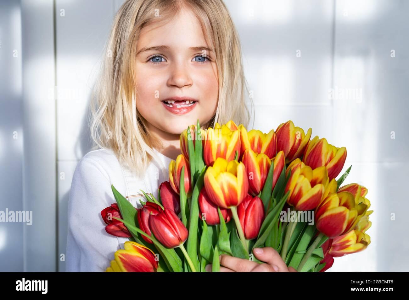 petite fille sans dents souriante avec un énorme bouquet de tulipes sur fond blanc avec lumière directe du soleil et ombres. Obtenir des fleurs. Bouquet cadeau Banque D'Images