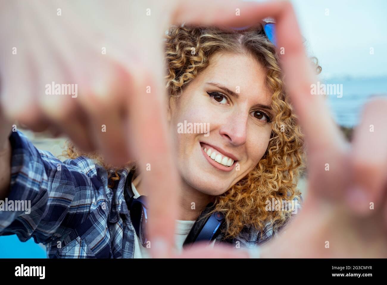 Gros plan portrait d'une jeune heureuse cheveux bouclés femme caucasienne regardant à travers un cadre fait de ses doigts. Capturez le concept du moment. Banque D'Images