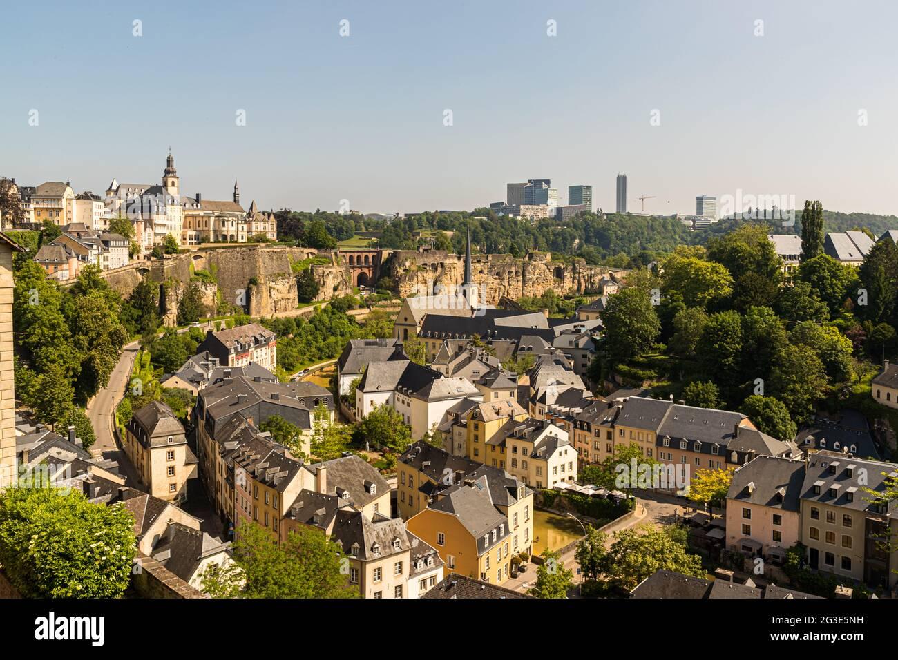 Vue depuis le mur de la ville de Luxembourg jusqu'au quartier inférieur de Grund, au bord de l'Alzette. En arrière-plan, la ligne d'horizon moderne sur le plateau de Kirchberg Banque D'Images