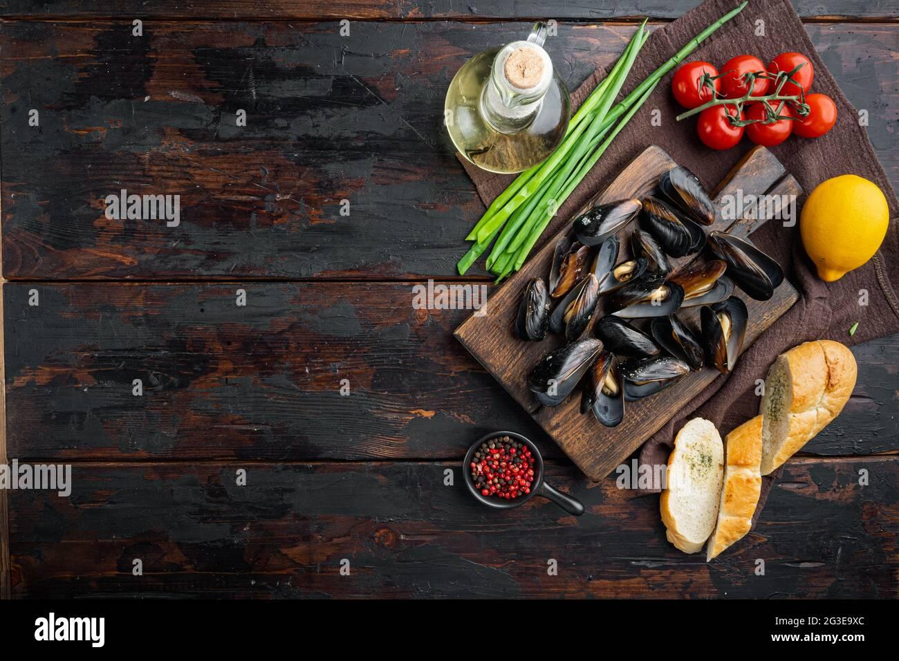 Moules cuites à la vapeur dans un décor de vin blanc, sur une planche à découper en bois, sur un arrière-plan de table en bois foncé, sur un plan de dessus, avec copyspace et espace pour le texte Banque D'Images