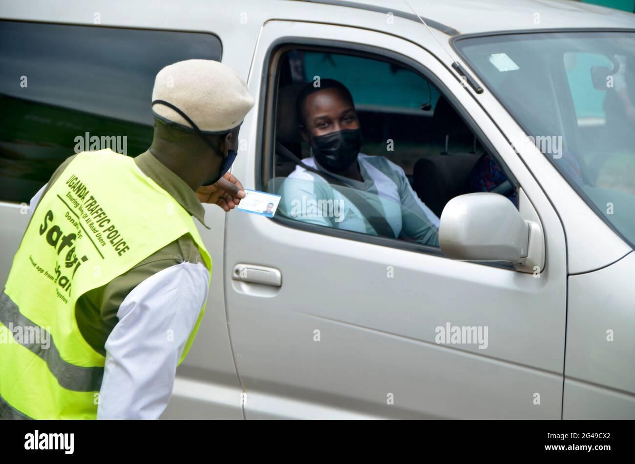 Kampala, Ouganda. 19 juin 2021. Un agent de police de la circulation vérifie les documents à un point de contrôle à Kampala, en Ouganda, le 19 juin 2021. Le Président ougandais Yoweri Museveni a annoncé vendredi une série de mesures visant à contenir la propagation rapide du nouveau coronavirus alors que le pays connaît une deuxième vague. Crédit: Nicholas Kajoba/Xinhua/Alamy Live News Banque D'Images