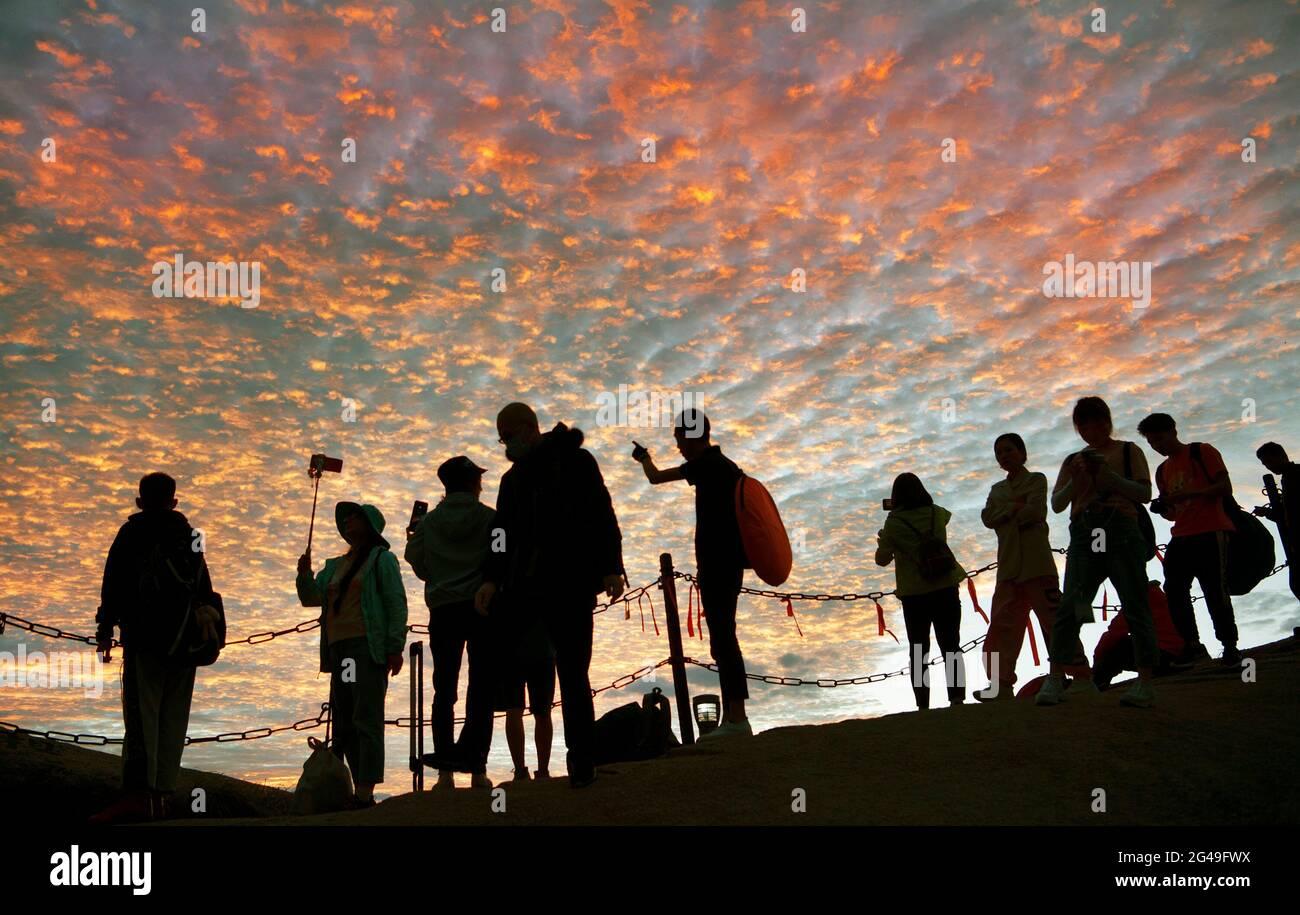 Huayin. 19 juin 2021. Les gens apprécient la lueur du coucher du soleil au Mont Huashan, dans la province de Shaanxi, dans le nord-ouest de la Chine, le 19 juin 2021. Credit: Tao Ming/Xinhua/Alamy Live News Banque D'Images